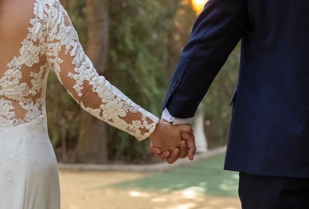 Feliz pareja de recién casados cogidos de la mano caminando en un parque