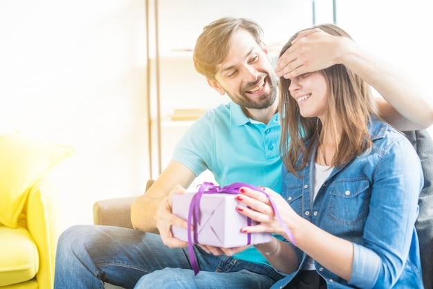 Feliz pareja con regalo de san valentín sentado en el sofá