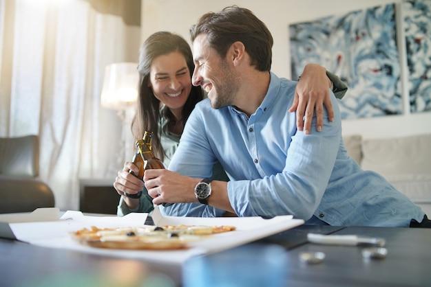 Feliz pareja relajada compartiendo una pizza en casa