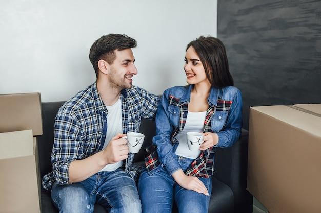 Feliz pareja relajándose en el sofá con café en apartamento nuevo