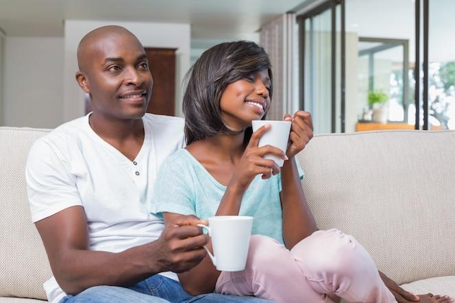 Feliz pareja relajante en el sofá tomando café