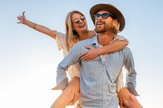 Feliz pareja riendo viajando en verano por mar, hombre y mujer con gafas de sol