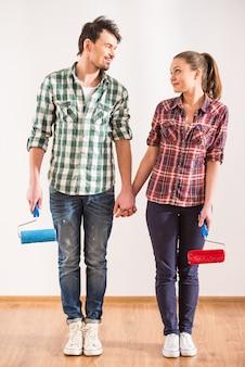 Feliz pareja con rodillo de pintura se miran.
