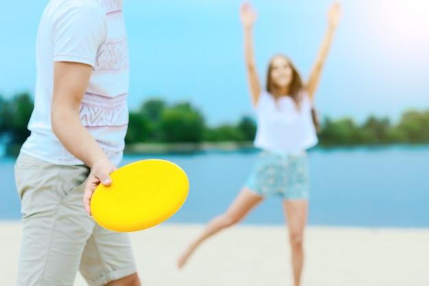 Feliz pareja romántica sonriente activa jugando frisbee hombre lanzar juego de disco