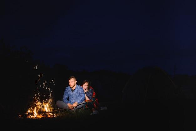 Feliz pareja romántica viajeros descansando en la hoguera cerca de la carpa turística brillante bajo el increíble cielo nocturno