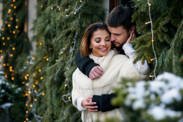 Feliz pareja en ropa de abrigo abrazándose unos a otros en el árbol de navidad con luces. vacaciones de invierno, navidad y año nuevo.