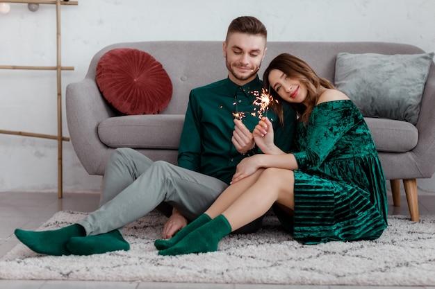 Feliz pareja en ropa verde elegante con bengalas, hombre y mujer embarazada sentada cerca del sofá, el día de san valentín