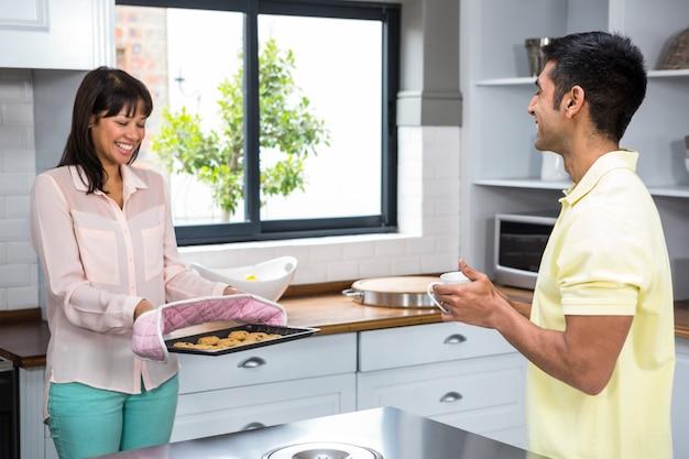 Feliz pareja sacando galletas del horno