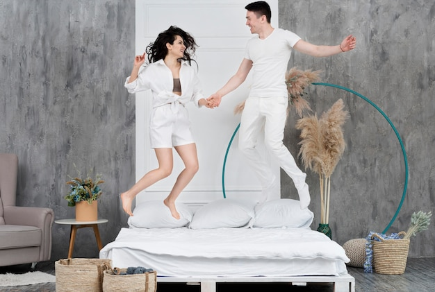 Feliz pareja saltando en la cama en su casa