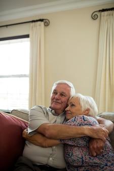 Feliz pareja senior abrazándose en la sala de estar en casa