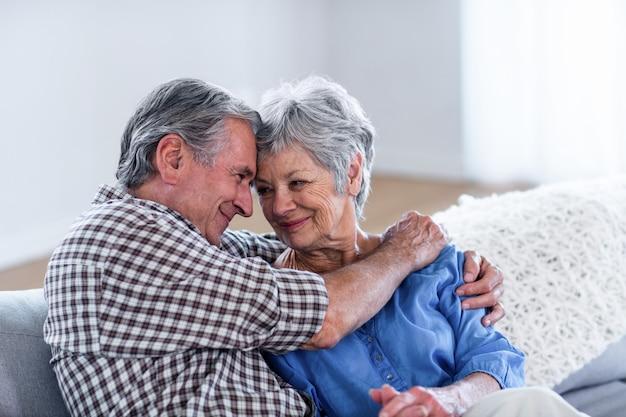 Feliz pareja senior abrazándose en el sofá