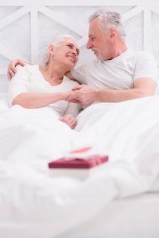 Feliz pareja senior acostado en cama con caja de regalo