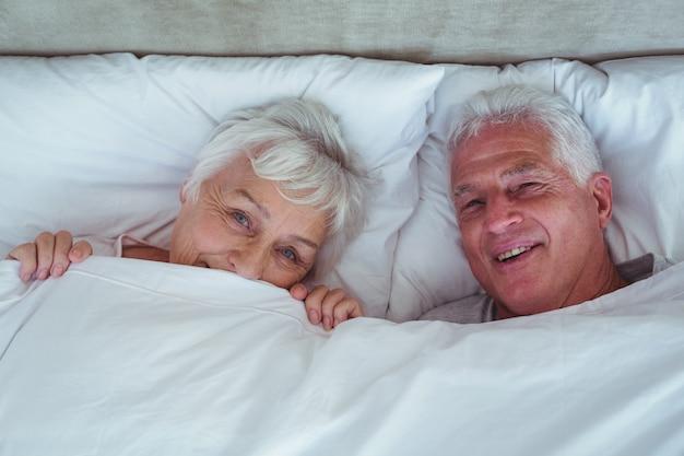 Feliz pareja senior acostado en la cama
