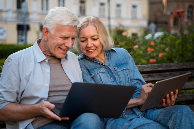 Feliz pareja senior al aire libre en un banco con ordenador portátil y tableta