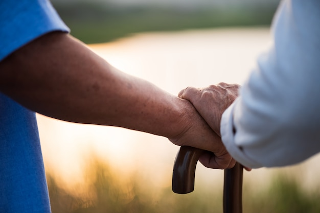 Una feliz pareja senior anciano asiático y una mujer cogidos de la mano