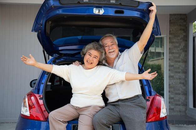 Feliz pareja senior asiática de pie en la parte trasera del coche y disfrutando de viaje.