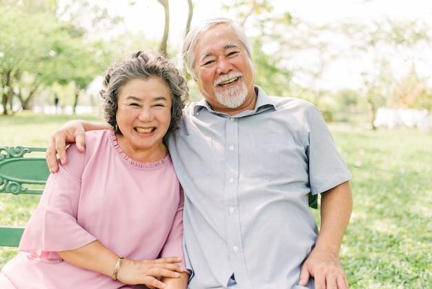 Feliz pareja senior asiática riendo y sonriendo mientras está sentado en el parque