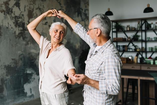 Feliz pareja senior bailando en la casa