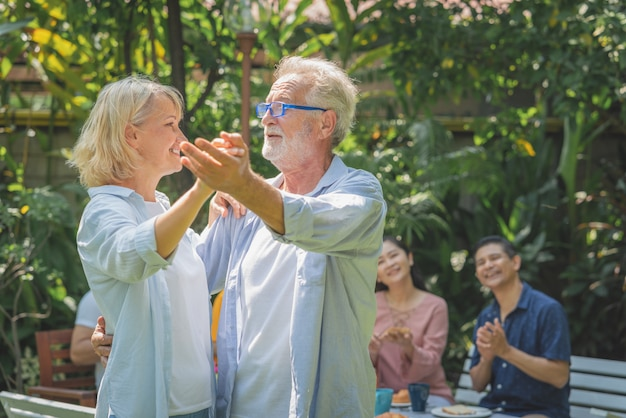 Feliz pareja senior bailando después del desayuno en la mañana con su familia en el jardín de su casa