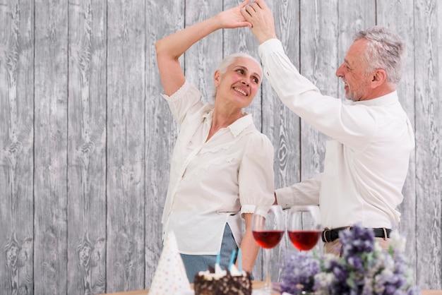 Feliz pareja senior bailando en la fiesta de cumpleaños