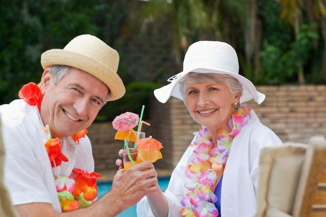 Feliz pareja senior bebiendo cócteles y brindando unos a otros