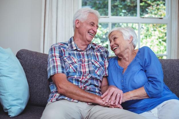 Feliz pareja senior cogidos de la mano en casa