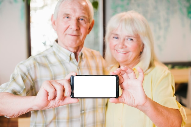 Feliz pareja senior demostrando móvil