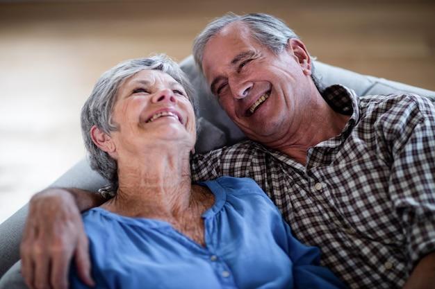 Feliz pareja senior descansando en el sofá y sonriendo