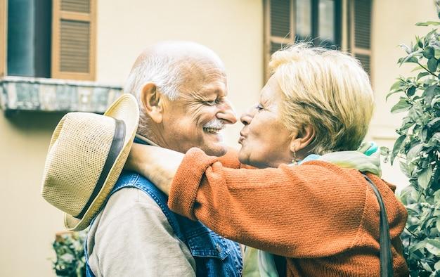 Feliz pareja senior divirtiéndose besándose al aire libre en vacaciones de viaje