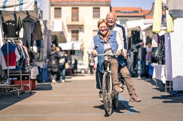 Feliz pareja senior divirtiéndose con bicicleta en el mercado de pulgas