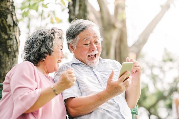 Feliz pareja senior emocionante con teléfono inteligente