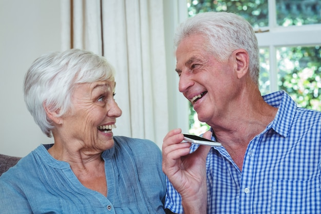 Feliz pareja senior escuchando música a través del teléfono