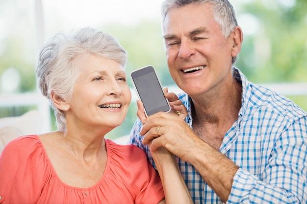 Feliz pareja senior escuchando smartphone en el sofá
