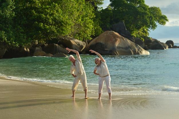 Feliz pareja senior haciendo ejercicio en verano en la orilla del mar