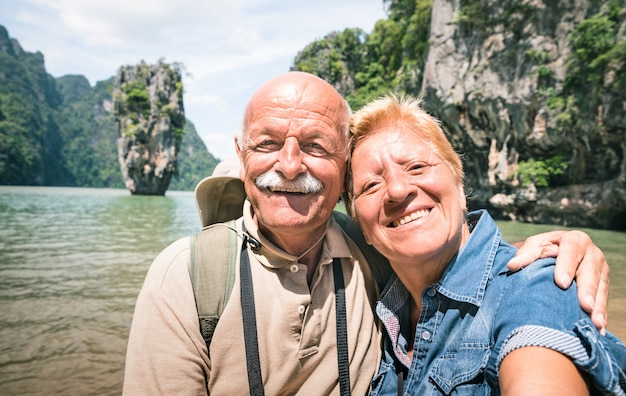 Feliz pareja senior jubilada teniendo viaje selfie alrededor en tailandia