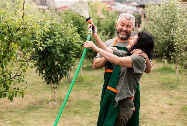 Feliz pareja senior con manguera de agua