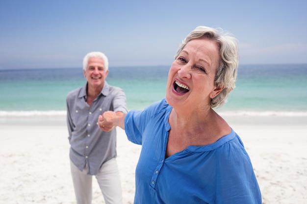 Feliz pareja senior mano en la playa