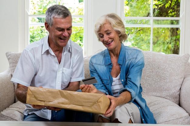 Feliz pareja senior con paquete y tarjeta de débito en casa