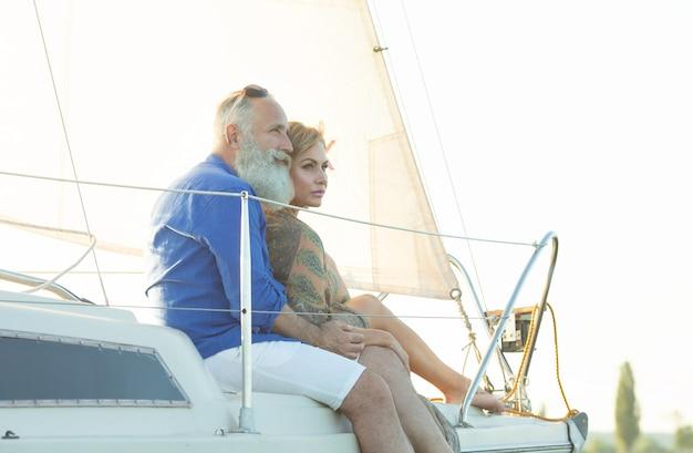 Feliz pareja senior de pie al lado del barco de vela o cubierta de yates flotando en el lago.