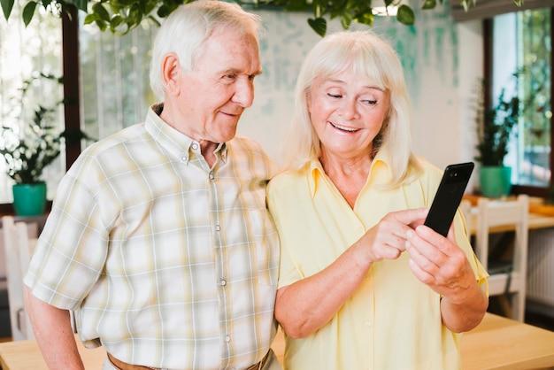 Feliz pareja senior de pie en la cafetería y mensajes de texto en el móvil