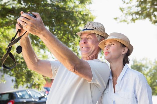 Feliz pareja senior posando para una selfie en un día soleado