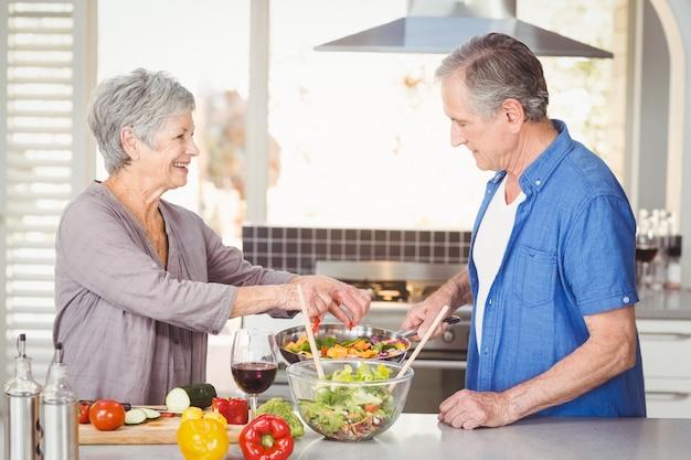 Feliz pareja senior preparando la comida