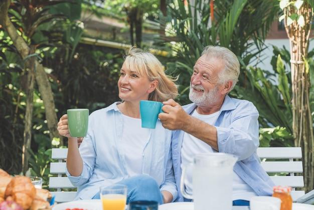 Feliz pareja senior relajante tomando café en la mañana en el jardín de su casa