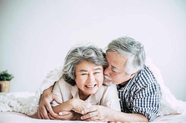 Feliz pareja senior riendo en el dormitorio