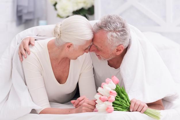 Feliz pareja senior romántica en la cama con flores de tulipán en la mano