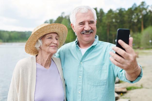 Feliz pareja senior romántica en ropa casual haciendo selfie en entorno natural en verano