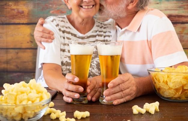 Feliz pareja senior sentada en una mesa de madera brindando con dos vasos de cerveza y papas fritas. marido besa a su esposa