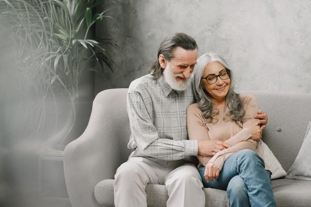 Feliz pareja senior sentada en el sofá en casa y hablando. concepto de tiempo de calidad.