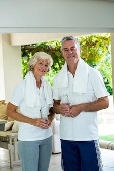 Feliz pareja senior sosteniendo botellas de agua