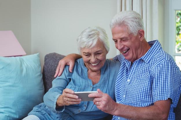 Feliz pareja senior con teléfono